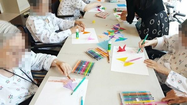 색종이로 나비를 접고 그 이외의 풍경들은 그림으로 그려보는 미술치료활동을 하고 계신 모습.