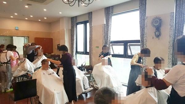 주님의교회 이미용 봉사팀이 방문해 어르신들의 머리카락을 다듬어 드리고 계신 모습.