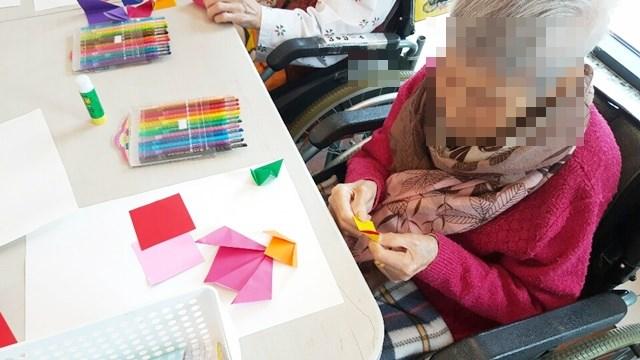 미술치료활동으로 색종이로 튤립꽃을 만들어 예쁜 꽃병 작품을 만들고 계신 어르신들의 모습.