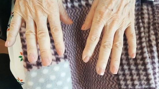 어르신들의 손톱을 깔끔하게 깎아드리고 손톱에 영양제 및 매니큐어를 발라드리고 있는 모습.
