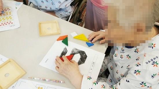 두뇌운동에 도움이 되는 퍼즐놀이, 칠교놀이, 활동지 풀이를 통해 인지활동을 하고 계신 모습.