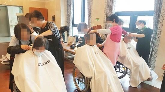 주님의 교회 이미용 봉사팀이 방문해 어르신들의 머리카락을 다듬어 드리고 계신 모습.