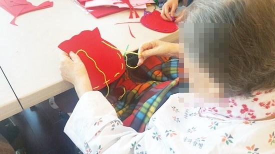 미술치료활동으로 펠트지, 털실을 활용해 소지품을 담을 수 있는 주머니를 만들고 계신 어르신들의 모습.