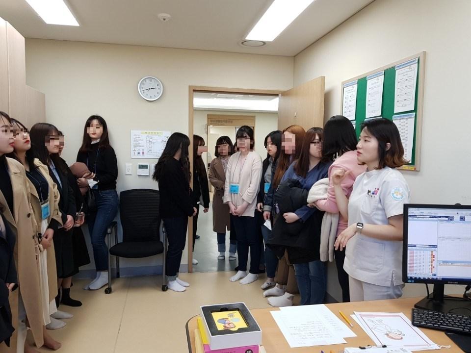 강남구립 행복요양병원 재활치료부 김본이 팀장이 신성대학 작업치료과 학생들에게 작업치료실을 설명하는 사진입니다.